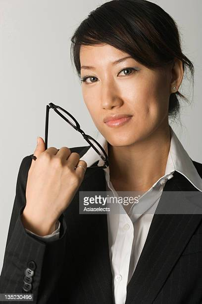 Portrait of a businesswoman holding a pair of eyeglasses and smirking