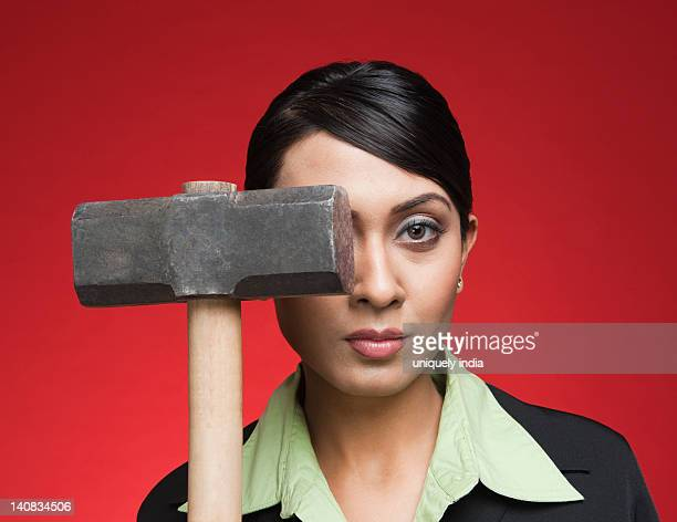 Portrait of a businesswoman holding a sledgehammer