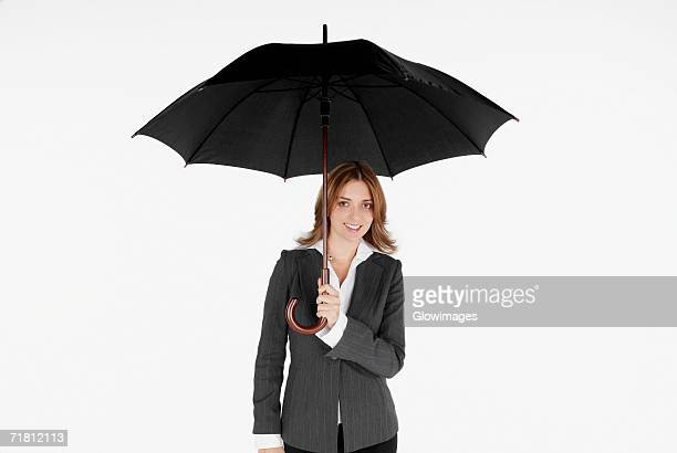 Portrait of a businesswoman holding an umbrella and smiling