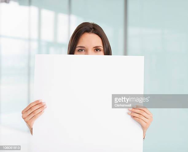 Portrait of a businesswoman holding up blank white paper