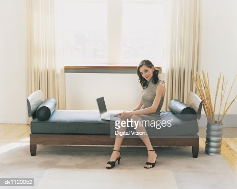 Portrait of a Businesswoman in a Hotel Room Sitting on a Chaise Lounge With a Laptop