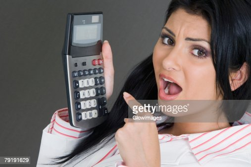 Portrait of a businesswoman pointing at a calculator : Foto de stock