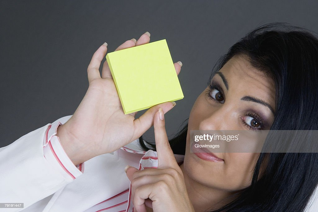 Portrait of a businesswoman pointing towards a blank adhesive note : Foto de stock