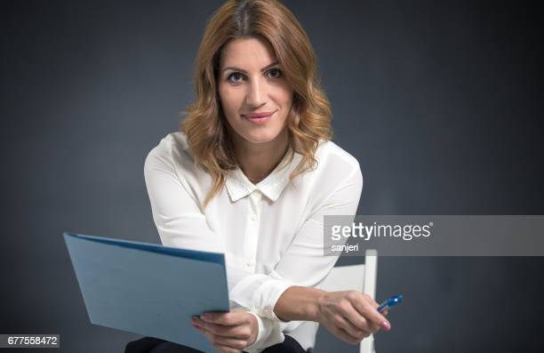Portrait of a Businesswoman Sitting and Holding a Paper Folder, Carrier