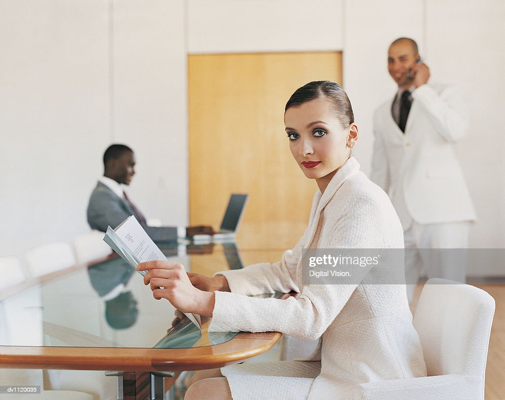 Portrait of a Businesswoman Sitting at a Table and Businessmen in the Background : Stock Photo