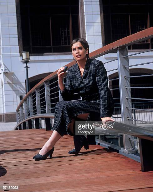 portrait of a businesswoman sitting on a railing holding a pager