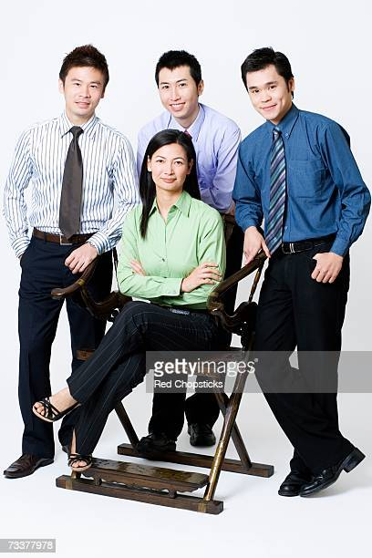 Portrait of a businesswoman sitting with three businessmen standing beside her
