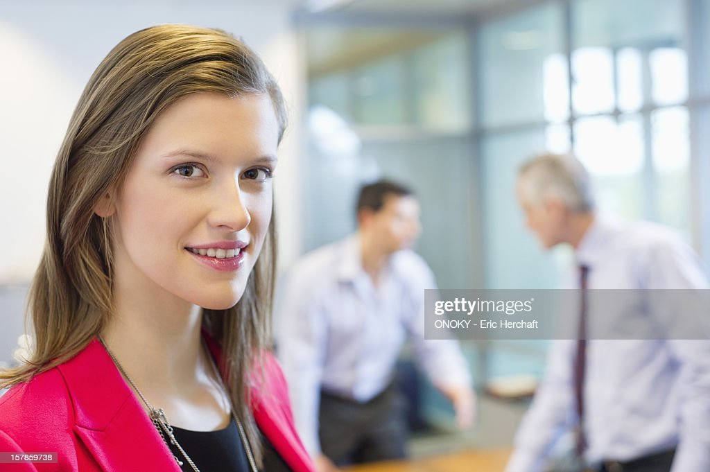 Portrait of a businesswoman smiling in an office with her colleagues discussing in the background : Stock Photo
