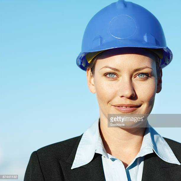 Portrait of a businesswoman smiling, wearing a hard hat