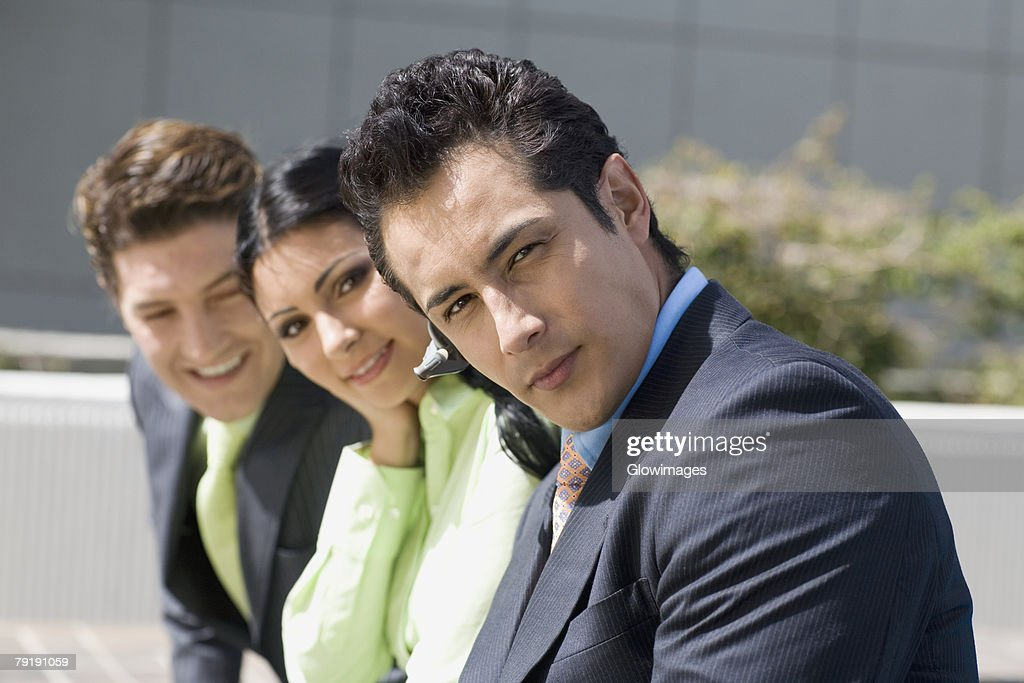 Portrait of a businesswoman smiling with two businessmen : Foto de stock