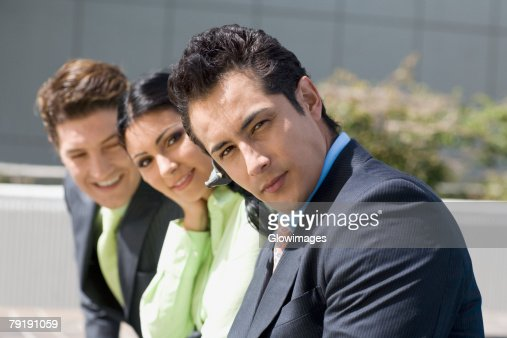 Portrait of a businesswoman smiling with two businessmen : Foto de stock