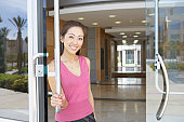 Portrait of a businesswoman standing at the entrance door of an office