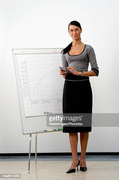 Portrait of a businesswoman standing with a calculator beside a whiteboard