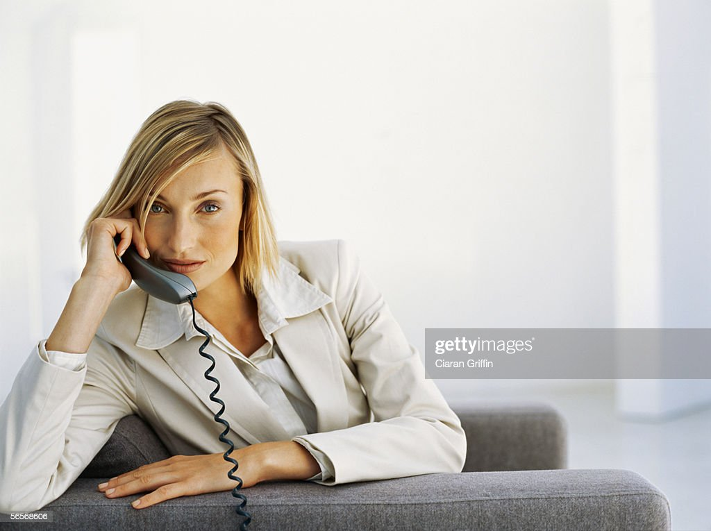 portrait of a businesswoman talking on a telephone in an office : Stock Photo