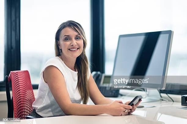 Porträt einer Geschäftsfrau mit Handy im Büro