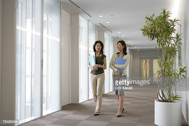 Portrait of a businesswoman walking together with her colleague in an office corridor and smiling
