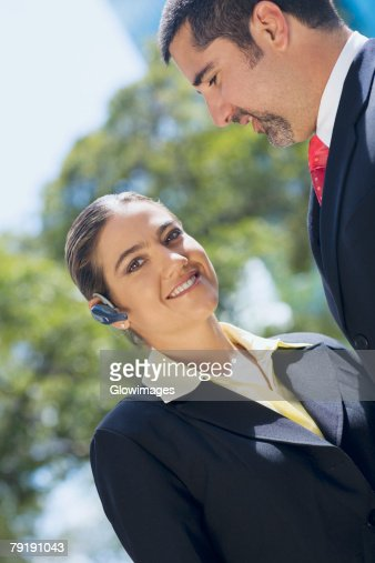 Portrait of a businesswoman wearing a hands free device with a businessman smiling beside her : Stock Photo