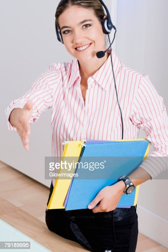 Portrait of a businesswoman wearing a headset and carrying files : Stock Photo