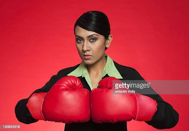 Portrait of a businesswoman wearing boxing gloves
