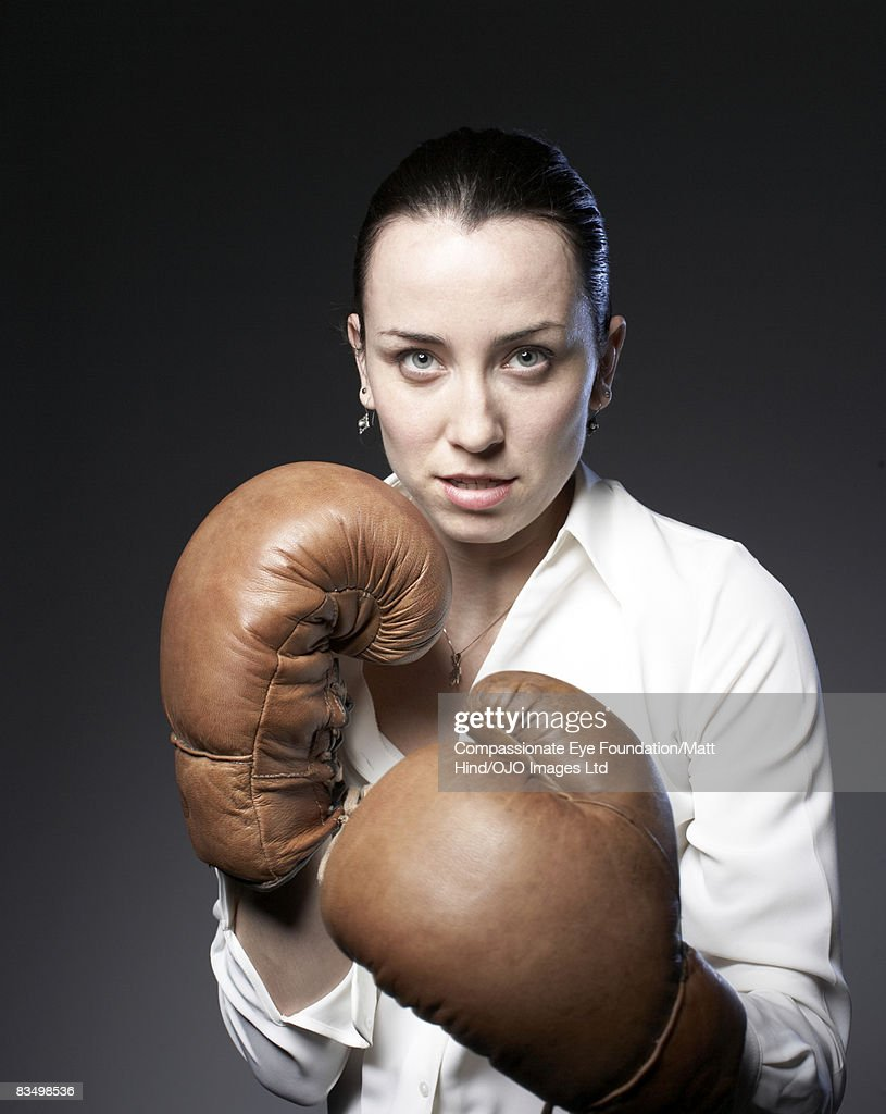 Portrait of a businesswoman wearing boxing gloves : Stock Photo