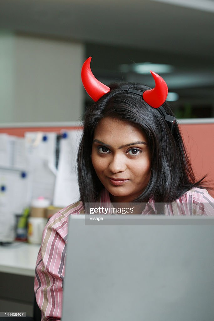 Portrait of a businesswoman wearing horns with laptop : Stock Photo