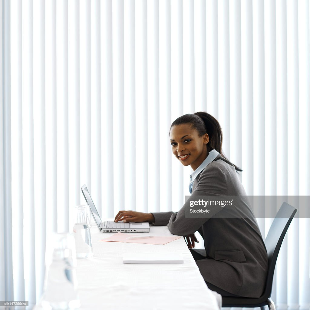 portrait of a businesswoman working on laptop and smiling : Stock Photo