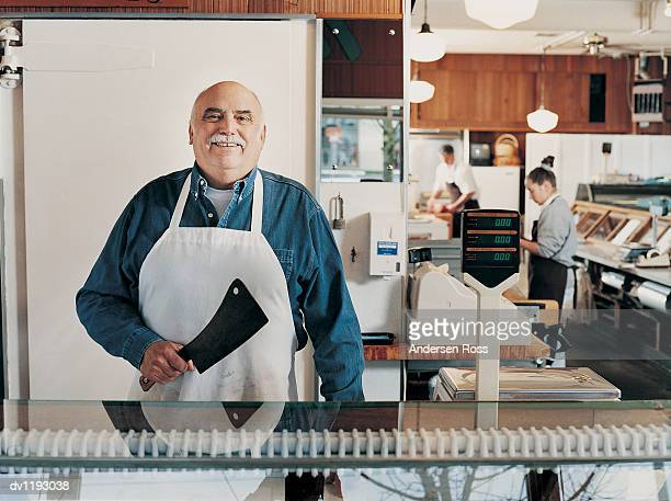 Portrait of a Butcher Standing Behind a Checkout Counter in His Shop and Holding a Cleaver