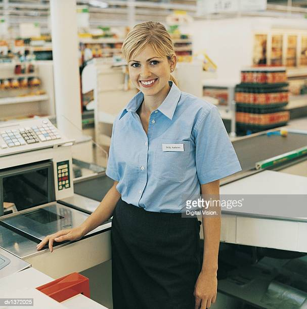 Portrait of a Cashier Standing at a Supermarket Checkout Counter