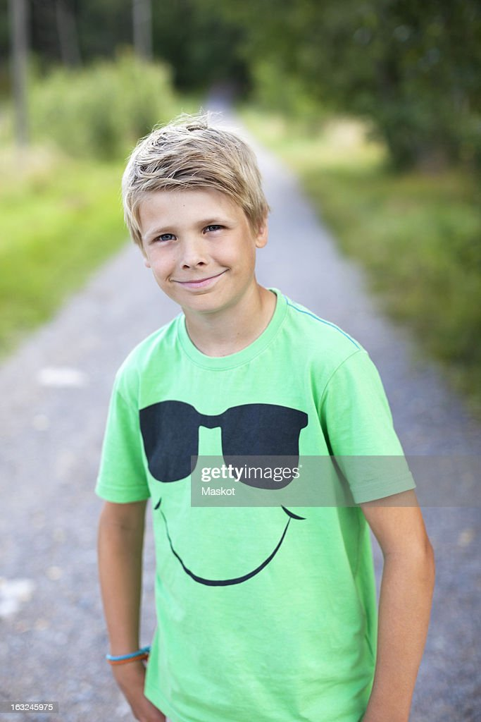 Portrait of a Caucasian pre-adolescent boy standing on road smiling : Stock Photo