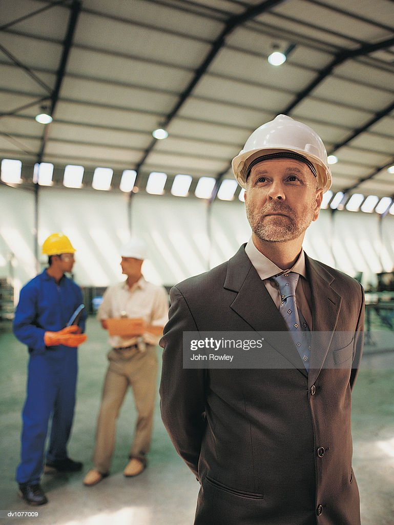 Portrait of a CEO Standing in a Factory With Two Factory Workers in the Background : Stock Photo