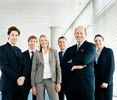 Portrait of a CEO With His Team of Business Executives Standing by a Window