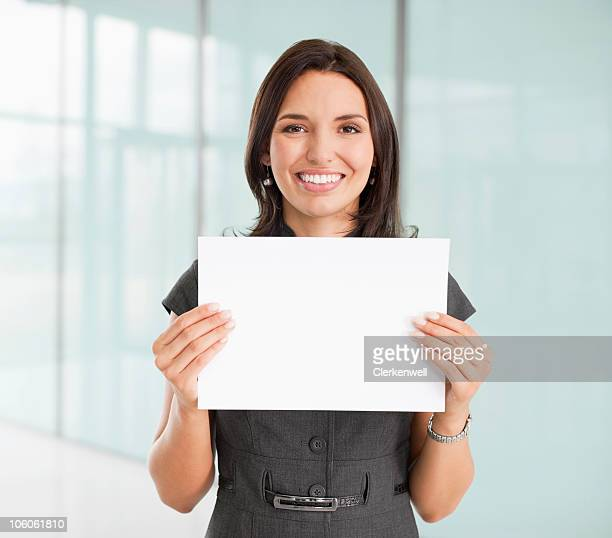 Portrait of a cheerful businesswoman standing with blank white paper