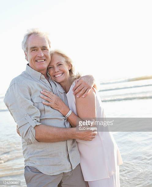 Portrait of a cheerful couple hugging on beach