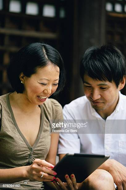 Portrait of a cheerful Japanese couple using tablet outdoors