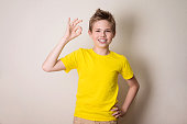 Portrait of a cheerful kid in braces showing okay gesture. Health, education and people concept.