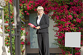 Portrait of a cheerful senior real estate agent with clipboard