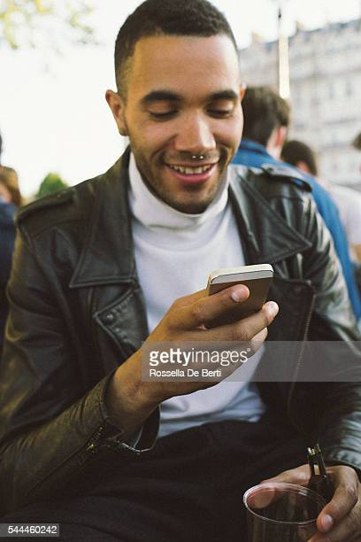 Portrait of a cheerful young man looking at his smartphone
