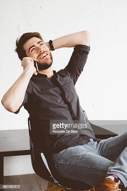 Portrait of a cheerful young man on the phone indoors