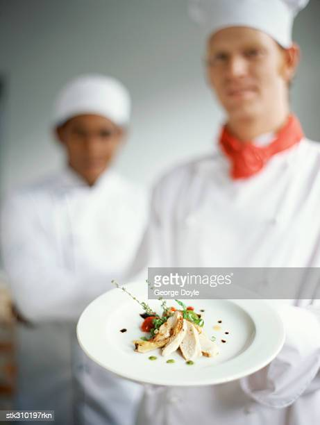 portrait of a chef holding a plate of food