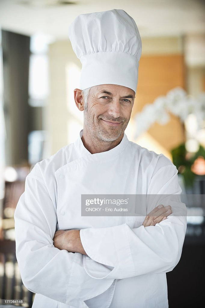 Portrait of a chef smiling with arms crossed : Stock Photo