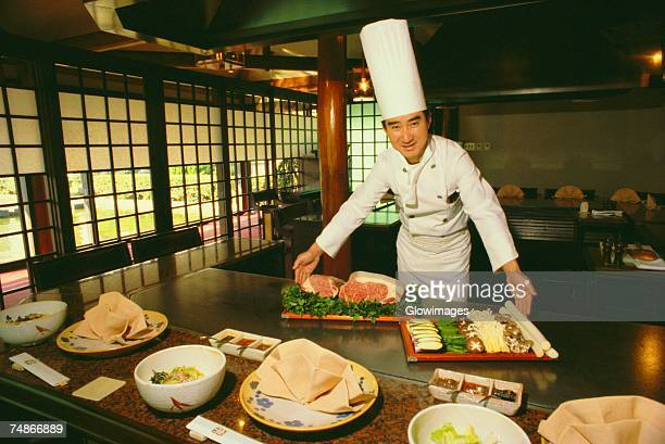 Portrait of a chef smiling with trays of food in front of him, Tokyo Prefecture, Japan