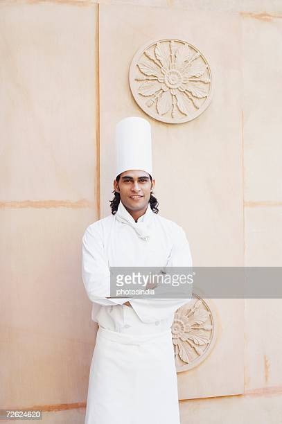 Portrait of a chef with arms crossed standing in front of a wall