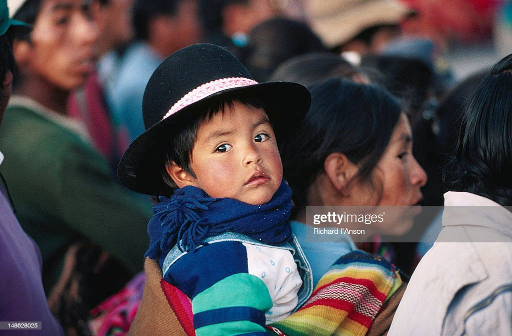 Portrait of a child wearing a hat, being carried on someone's back - Cuzco : Stock Photo