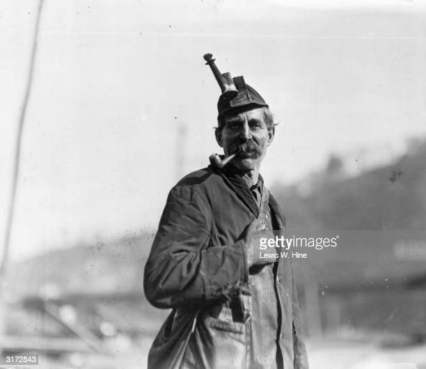 Portrait of a coal miner smoking a pipe and wearing an oil lamp torch hat West Virginia His clothes hands and face are covered in soot