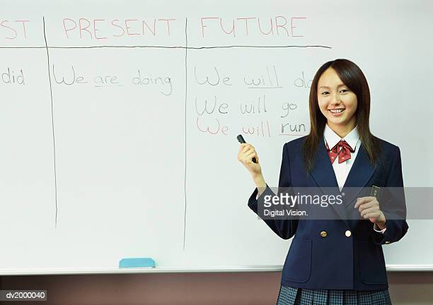 Portrait of a College Student Standing by a White Board in a Classroom