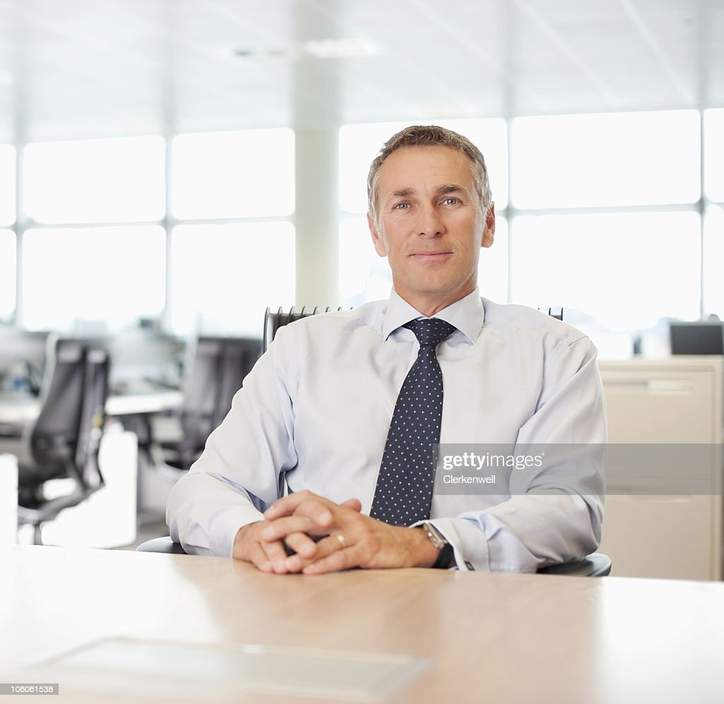 Portrait of a confident business executive sitting at desk : Stock Photo