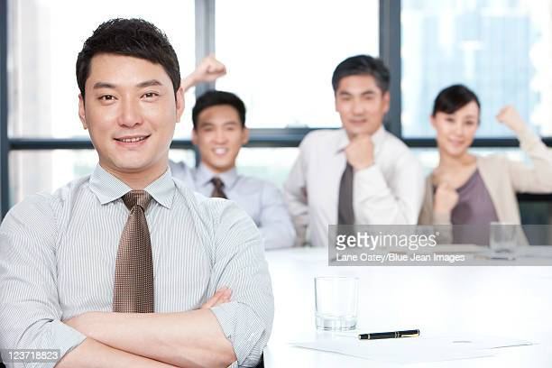 Portrait of a Confident Businessman with Business Team Cheering in Background