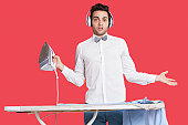 Portrait of a confused man in formals ironing as he listens to music over red background