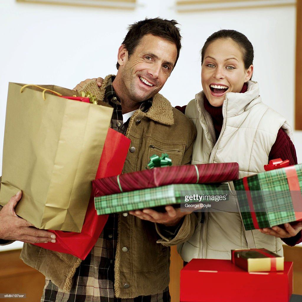 portrait of a couple carrying bags of Christmas presents : Stock Photo