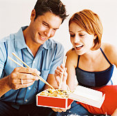 portrait of a couple eating Chinese take-out with chopsticks